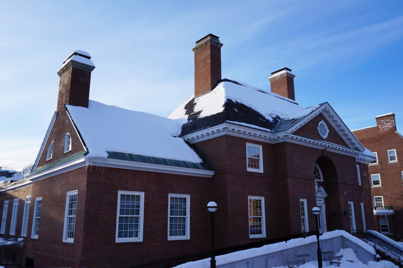 Outside of a red brick building with fresh snow on the roof